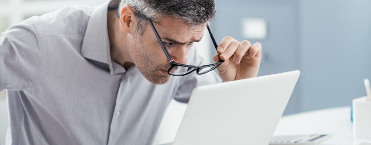 Man mit Brille schaut angespannt auf Laptop