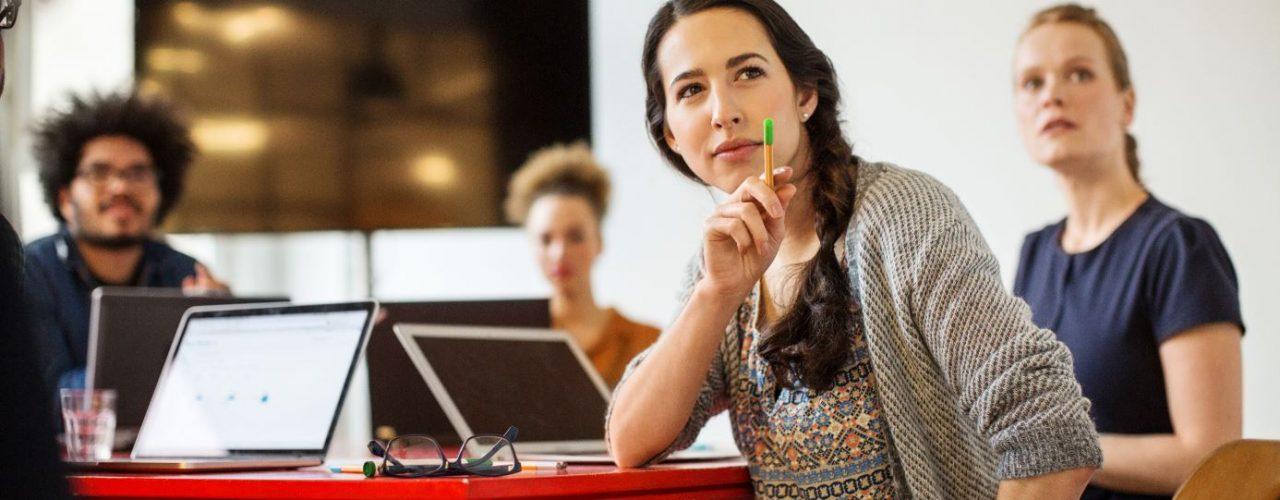 Frau im Meeting zeigt mit Stift